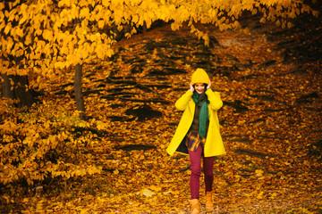 beautiful young woman walking outdoors in autumn