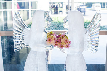 Romantic frame of Ice angel sculpture looking together with beautiful bouquet flower presentation in wedding ceremony, Blurred image from foggy of ice sculpture