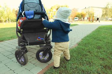 Cute little baby near stroller outdoors