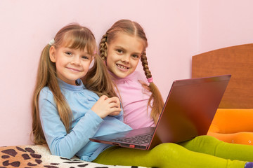 Two girls sitting on a bed with a laptop and a fun look into the frame