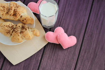 Glass of milk, croissants and felted hearts