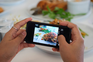 Using hands to take food's picture by smart phone.