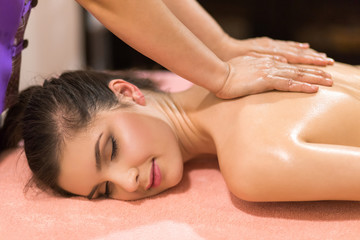 Beautiful woman having a wellness back massage and feeling visib
