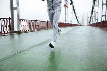 Cropped image of Man running on bridge