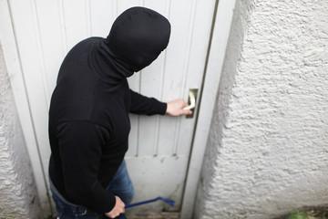 Maskierter Einbrecher an der Keller Tür