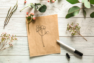 Paper with drawing of hypericum pink on white wooden background
