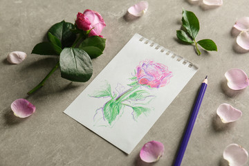 Rose and paper with drawing on grey background