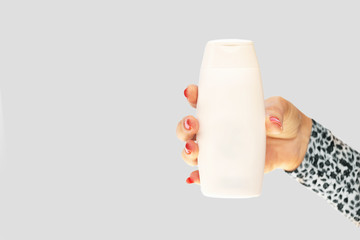 Female's hand with red nails holding a white plastic bottle