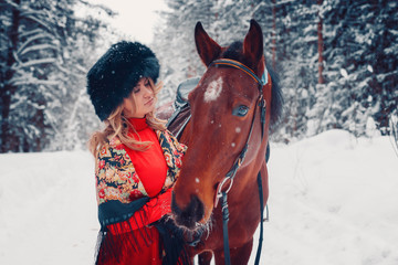 portrait of a beautiful girl and handsome stallion, horse in the winter on the nature