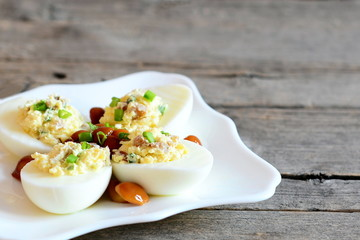 Basic stuffed eggs on a plate isolated on old wooden background with copy space for text. Hard-boiled eggs stuffed with cheese, mushrooms and green onions. Holiday appetizer recipe. Closeup