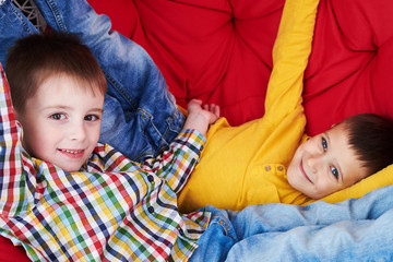 Close-up of two boys relaxing on a soft red couch, lying lazy wh