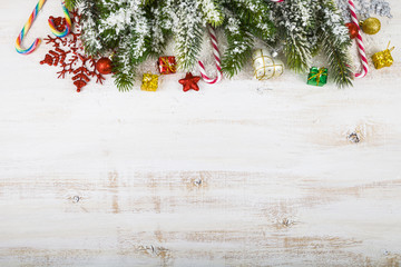 Christmas decorations, gifts and fir branches on a wooden table.