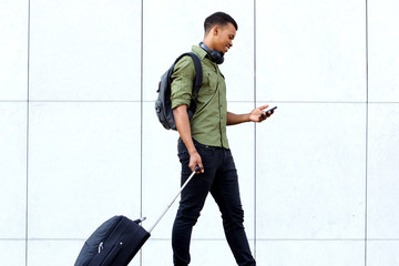 young traveling man walking with suitcase and cellphone