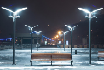 Bench on a snowy square illuminated by lamps with reflectors.