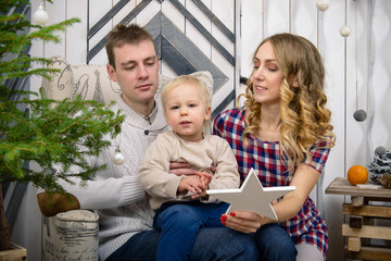 family photo: Mom, dad and baby in Christmas