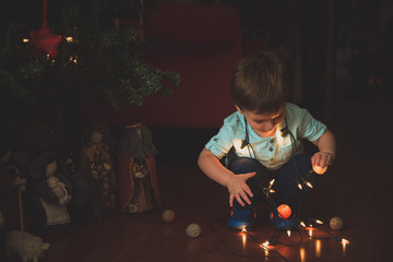 Little boy playing with garland