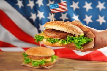 Male hand holding tasty American hamburger, closeup