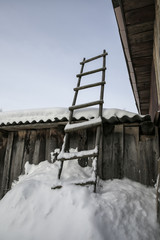 Wooden ladder. Standing in the snowdrift. Leaning against barn w