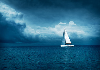 Foto auf AluDibond Segeln White Yacht Sailing in Stormy Sea. Dark Thundery Night Background. Dramatic Storm Cloudscape. Danger in Sea Concept. Cold Toned Photo with Copy Space.
