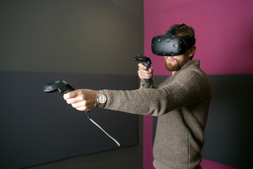 bearded man using the virtual reality glasses and two gamepad