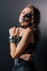 Portrait of young woman with skull make-up.