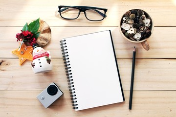 Business, work day, christmas or new year concept : Workspace desk with notebook, pencil, pine cones in tea wooden cup, eye glasses, christmas decoration and small action camera on wooden background