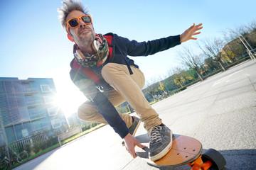 Mature man skateboarding in the street