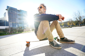 Trendy urban guy sitting on skateboard in park