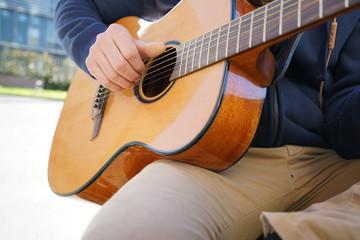 Closeup of guitar, musician playing outside