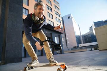 Mature man skateboarding in urban environment, filming himself