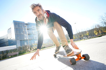 Mature man skateboarding in the street
