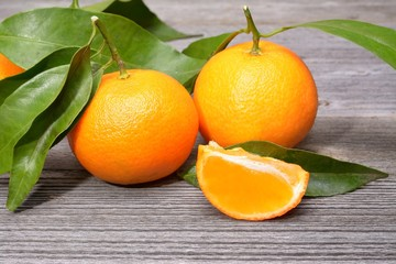 Wall Mural - tangerines, peeled tangerine and tangerine slices on a white wooden table