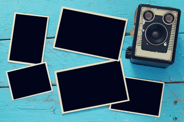 Top view of empty photo frames next to old camera
