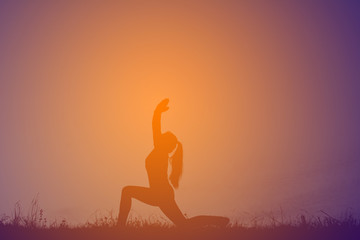 Silhouette women yoga in nature at the sky sunset, color of vintage tone