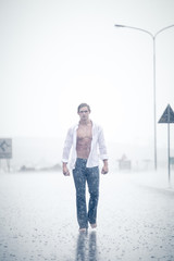 A Good looking male model walking in a streat in the pouring rai