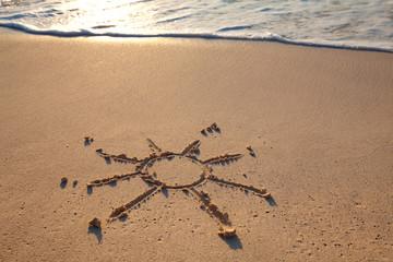 petit soleil dessiné sur le sable à la mer