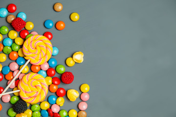 Delicious colorful candies on a gray wooden background. Conceptual image symbolizing the too frequent use of sweets. Picture with space for text
