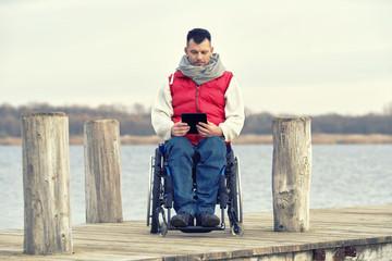 Integration behinderter Menschen, Rollstuhlfahrer mit tablet