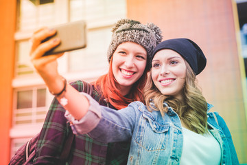 two young handsome caucasian blonde and redhead hair women hugging outdoor in the city, holding smartphone, taking selfie, smiling - social network, communication, vanity concept - colorful filtered