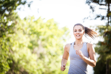 Close up image of a female fitness model running / exercising in a street in a suburban area