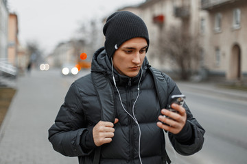 Handsome young man in winter clothing walking in the city and listen music