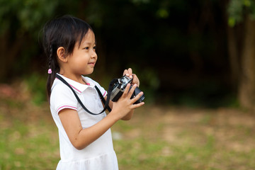 Beautiful child girl taking camera at the nature field.