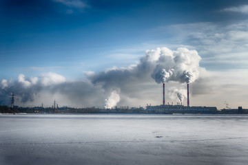 Power plant smokes in blue dramatic sky in a winter city. Free copyspace text