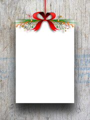 Blank frame hanged by red Christmas ribbon against wooden background