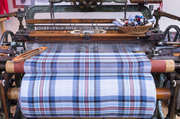Highland tartan fabric on traditional weaving loom at Lochcarron Weavers in Lochcarron in the Highlands of Scotland, United Kingdom, Europe