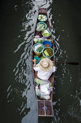 Vendor paddles boat with vegetables for sail, Thailand