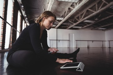 Dancer sitting on floor and using digital tablet