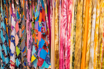 Rows of colourful batik hanging at a market stall in Bangkok, Thailand..