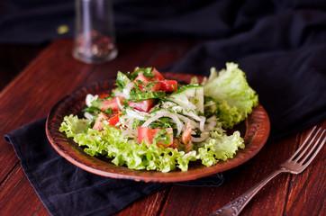 Тарелка с салатом из свежих овощей на деревянном столе, рустик