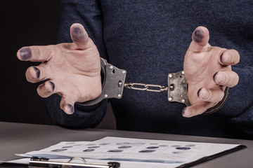 hands with handcuffs lying on top of fingerprint sheets.